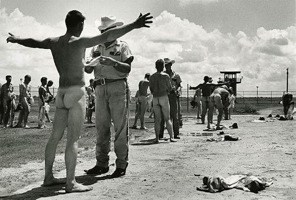 """Get up out of 'em.""  Looks exactly like the daily ritual after working all day.  That guard is probably checking the inmate's cap for a nail or mushroom.  Photo found on Google Images from Danny Lyon Prison Photography."