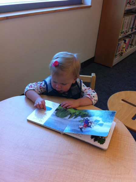 """Reading"" to herself at the library."