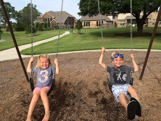 Learning to pump her legs on the swing with William.