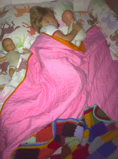 Cuddled up with her baby dolls in her big girl bed.